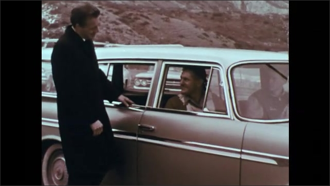 1960s: Man opens door of car for woman and children.  Men speak.