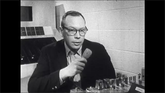 1960s: Dr. Paul M. Fitts points to experiment. Scientist speaks in microphone and student subject in headphones tests his reaction time on equipment. Student resets Reaction and Movement time clocks.