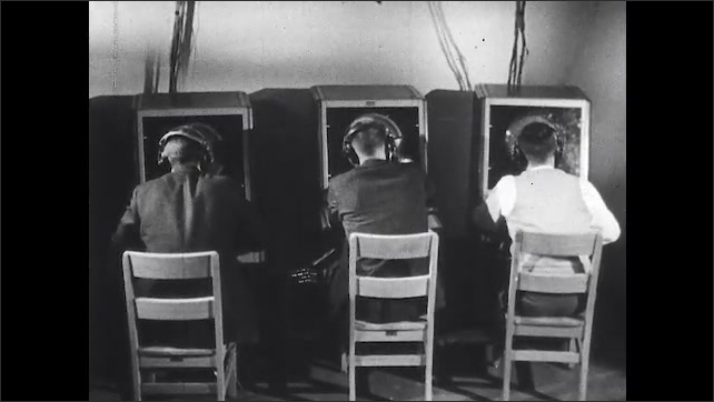 1960s: George Briggs explains in a simulated air traffic control tower room at Ohio State University. Test subjects sit at individual terminals as engineering psychologist watches and measures.