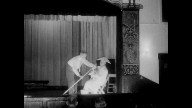 1950s: Man in robe in chair on stage, man puts duck in man's hands.