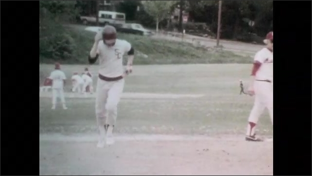 1980s: School baseball team plays. Boy looks determined, throws pitch, looks up. Boys throw baseball, run bases. Coach watches, score board.