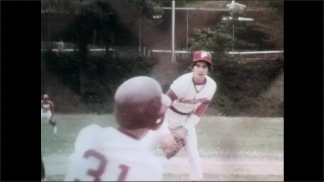 1980s: School baseball team, score board, coach paces, watches. Pitcher pitches, batter hits ball, runs bases. Coach gestures.