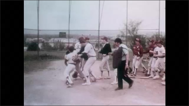 1980s: School baseball team plays, catcher catches ball, drops it, player slides through home base. Team rushes in. Boy talks, smiles, cleans dirt off cleats.
