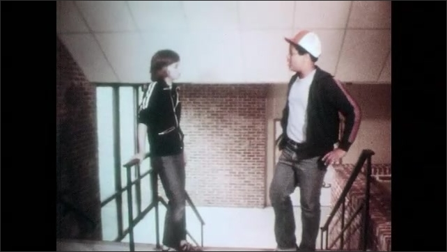 1980s: School, boys walk up stairs, talk, gesture, shake hands.