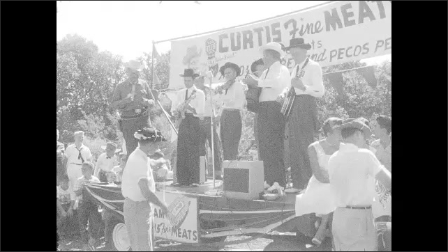 1960s: UNITED STATES: people watch procession. Band on stage. Curtis Fine Meat float. Man rides horse in street