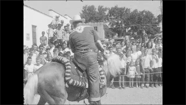 1960s: UNITED STATES: cowboy rides horse in street carnival. Horse performs for crowd. Crowd watch parade.