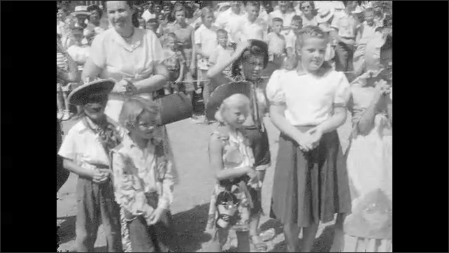 1960s: UNITED STATES: children stand on carnival float with cowboys. People in crowd