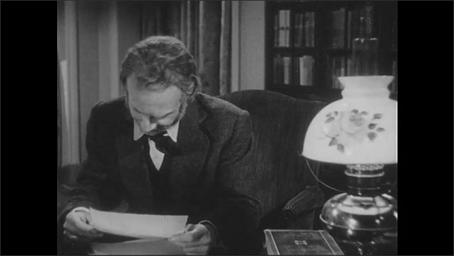 1940s: Man sits at desk, writes, picks up paper, reads, nods head. Man gets up from desk, walks over to woman in chair, talks with woman.