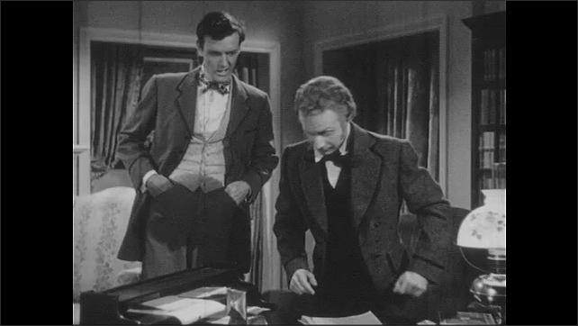 1940s: Woman walks away from men. Older man talks to younger man, walks to desk sits down. Younger man talks.