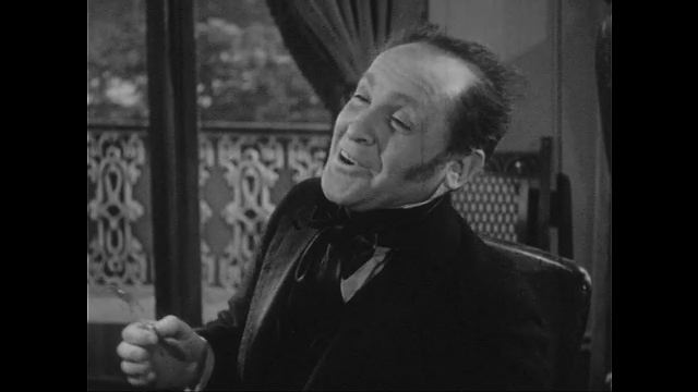 1940s: Man smiles and talks while holding eyeglasses in one hand. He puts his eyeglasses on as Holmes talks.