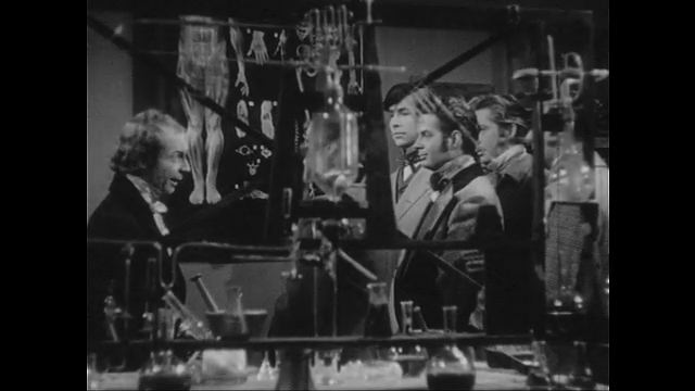 1940s: Holmes points to diagram and group of men watch in laboratory. Holmes looks into microscope. View of Brownstone.