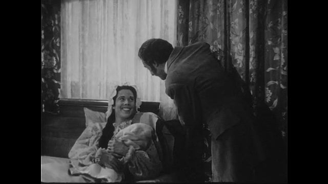 1940s: Woman hands baby to Holmes. Cut to view of hospital building.