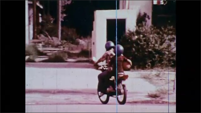 1970s: Man fills his car at an Amoco gas station. Van parked at the gas station. Two people ride on a motorcycle, one carrying a basketball. Men stand on the corner talking next to a parked truck.