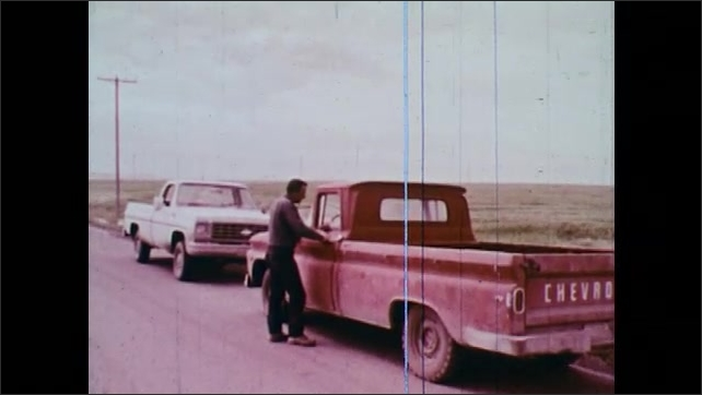 1970s: Red pick-up is pulled over by a white pick-up and the two drivers talk. Men talk on the town street next to parked cars.