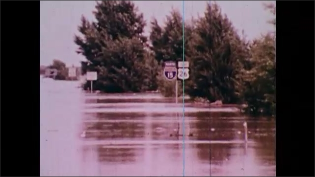 1970s: Aerial footage of farmland covered in flood waters after Teton Dam burst. Water covering the streets and downed bridges. Debris washes up against the shore.