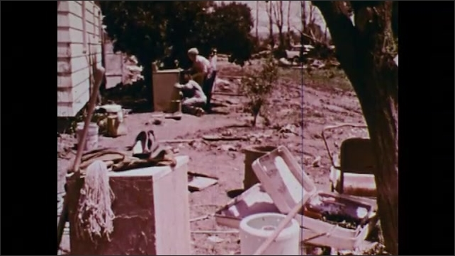 1970s: Couple loads debris into back of pick-up truck with pitchforks. Woman throws debris out window into a dumpster. Mud and silt covered belongings in the street. People shovel debris from street.