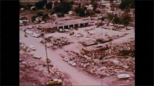 1970s: Aerial footage of flooded town and electric utility trucks in town to repair. Downed power lines and an oil tank.