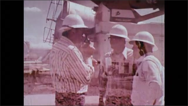 1970s: Transformer from substation set out to repair. Electricity utility workers on walkie-talkies. Workers help raise wooden power pole.