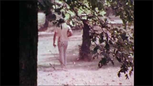 1970s: UNITED STATES: boys walk along woodland path. Man walks dogs in forest. Children walk by beach