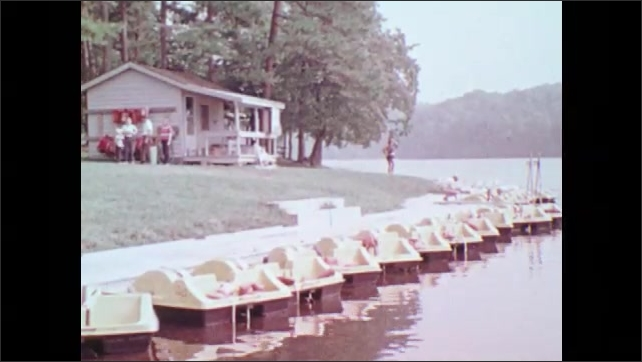 1970s: UNITED STATES: nuns sit at table by lake. Lady eats food. Holliday Lake State Park. Sailing boat on lake. Camper on campsite by tent. Bugs Island Lake.