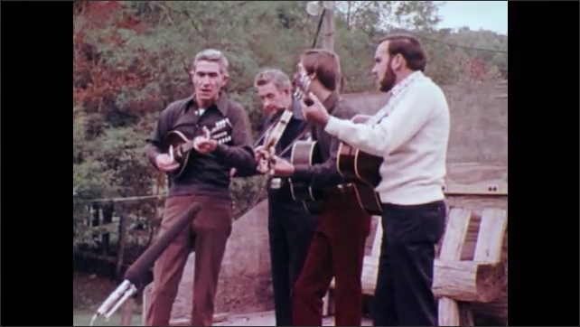 1970s: People sit in grass eating food. Woman holds baby. Four men play instruments in bluegrass band.