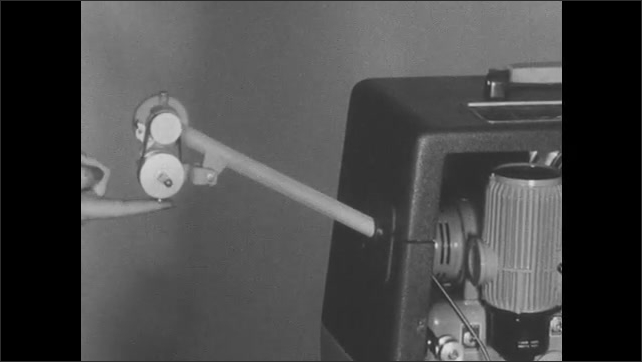 1950s: Woman removes empty reel from projector case, places feed reel arm into socket on top of case and take up reel arm into rear of case, touches gears. Woman loops belts over both feed reel arms.