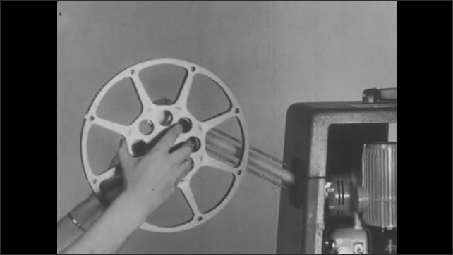 1950s: Woman flips switches on projector to off position, places film reel on top reel arm and empty reel on take up reel arm. woman unwinds film from reel, threads through projector case.
