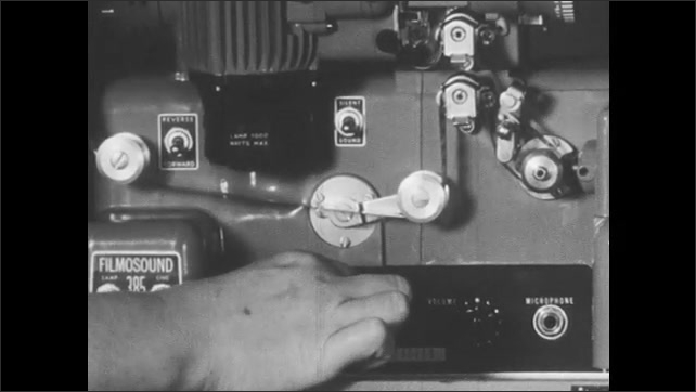 1950s: Woman turns knob on projector, spins dial to move film, moves knob back. Woman adjusts knobs and switches on projector, turns projector on.