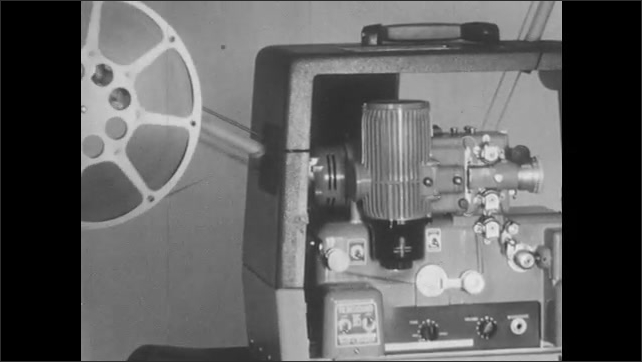 1950s: Woman flips switches and adjusts knobs on projector. Film runs through projector and onto take up reel. Woman turns off projector power switch.
