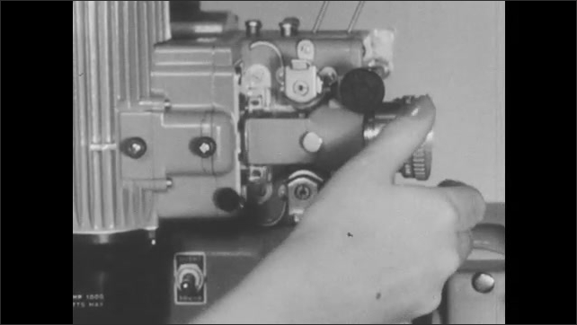 1950s: Film reels turn on Bell and Howell filmosound projector. Woman adjusts lens lock, pulls lens out of projector, wipes with cloth, replaces lens into projector.