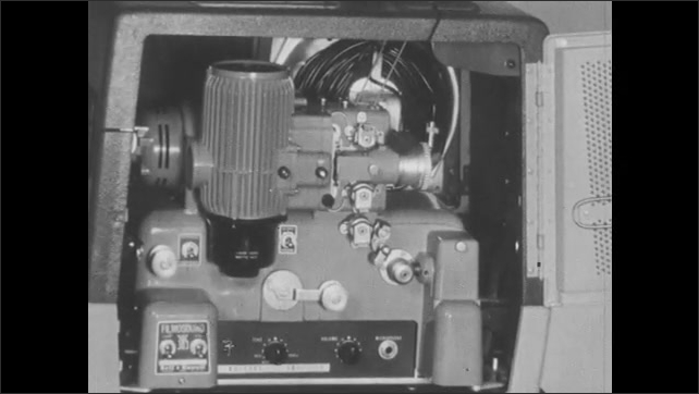 1950s: Woman holds Bell and Howell projector manual, opens manual. Bell and Howell projector. Film reels spin on projector.