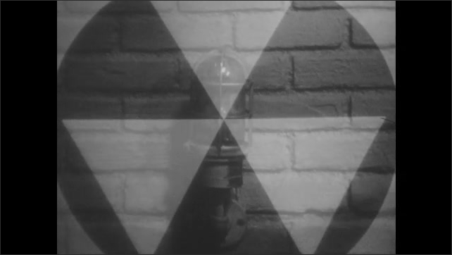 1960s: UNITED STATES: shadow on wall. Radiation symbol. People head for shelter. Warning light flashes on wall. Man carries box