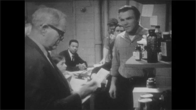 1960s: UNITED STATES: man takes bottle from shelf. Medical supplies in fallout shelter. Leaders meet inside fallout shelter