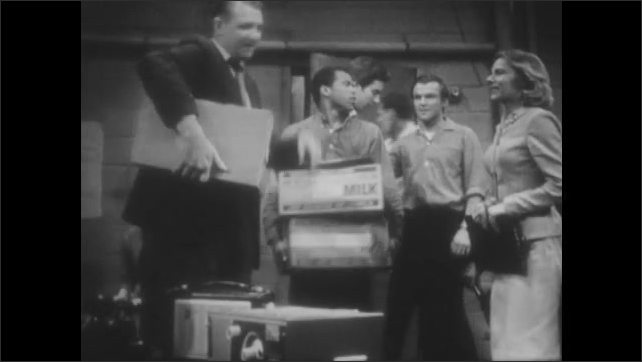 1960s: UNITED STATES: community leaders prepare fallout shelter. Men arrive with cardboard boxes in shelter. Close up of radio.