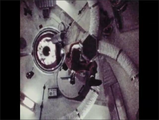 1970s: Space station in orbit. Astronaut moves through spacecraft.