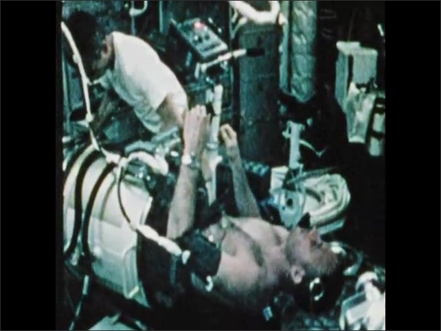1970s: Man lays in tube. Man rides exercise bike. Man monitors machines.