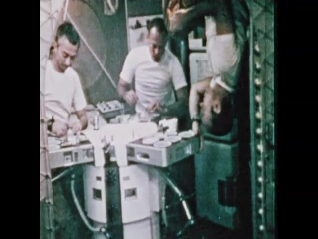 1970s: Astronauts stand at small table, eat. Man flips upside down in zero gravity.