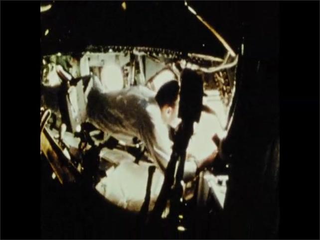1970s: Astronaut moves through spacecraft.