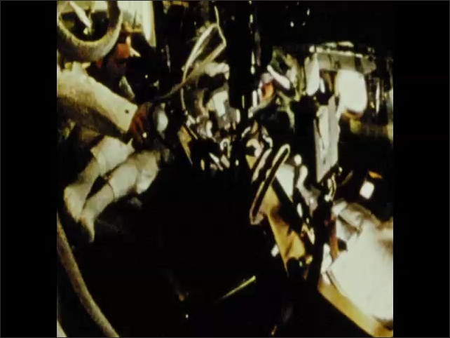 1970s: Astronaut moves through spacecraft. Astronaut sits at control panel.