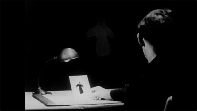 1950s: Man sits at desk holding picture. Ghost appears.
