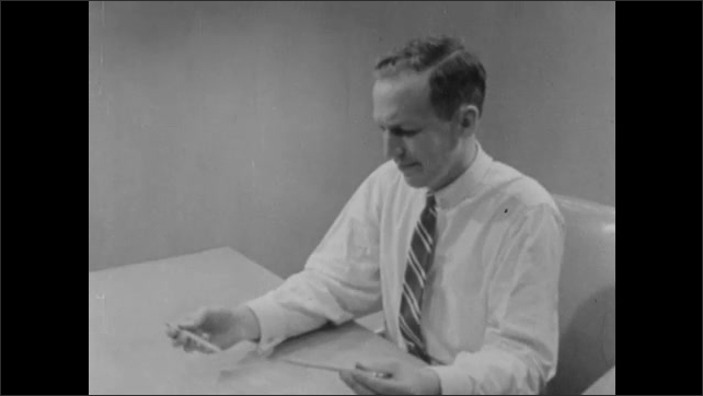 1950s: Man holds up two pencils, closes one eye, and moves pencils toward each other. Man frowns. Man holds up two pencils and moves them toward each other.