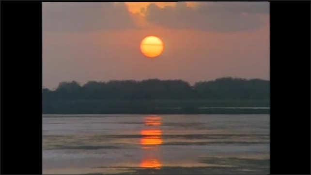 1990s: Sun sets over a body of water. Two girl students learn in a science lab from a scientist.