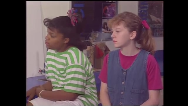 1990s: Scientist points to a chart depicting Electromagnetic Spectrum. Two girl students look on. Scientist holds up a prism. Prism in a dark room in front of a light projector. A rainbow appears.