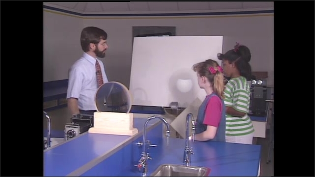1990s: Scientist holds up a white card in front of a lens and moves it back so the circle of light becomes smaller. Scientist moves the cardboard and demonstrates to two girl students.