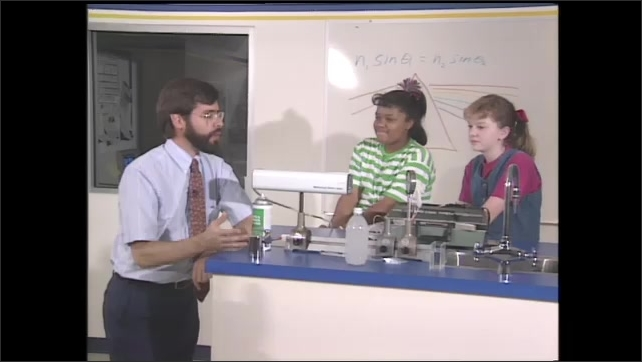 1990s: Scientist discusses laser light with two girl students in a science lab.