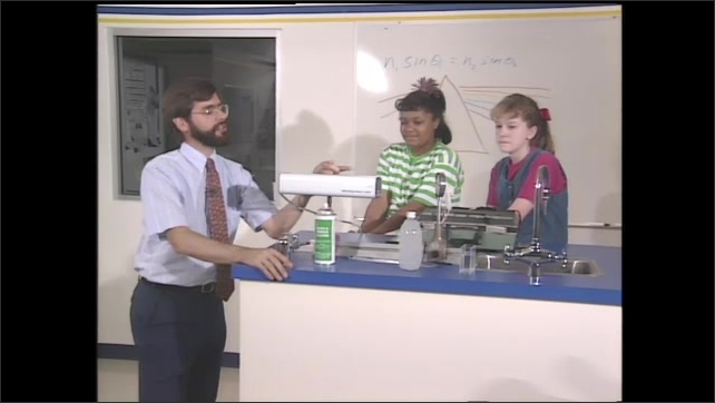 1990s: Scientist demonstrates laser light with two girl students in a science lab. Scientist sprays aerosol to demonstrate the red laser light. Laser light dances and makes shapes.