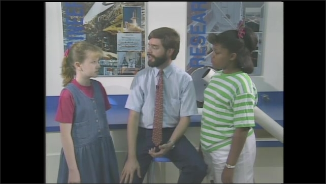 1990s: Scientist discusses laser light with two girl students in a science lab. Scientist is beamed up by laser light graphics. Two girl students are left amazed by disappearing scientist.