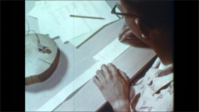 1960s: Man climbs ladder, steps into ruins. Man walks around ruins. Man sits at desk, compares lines on strips of paper.
