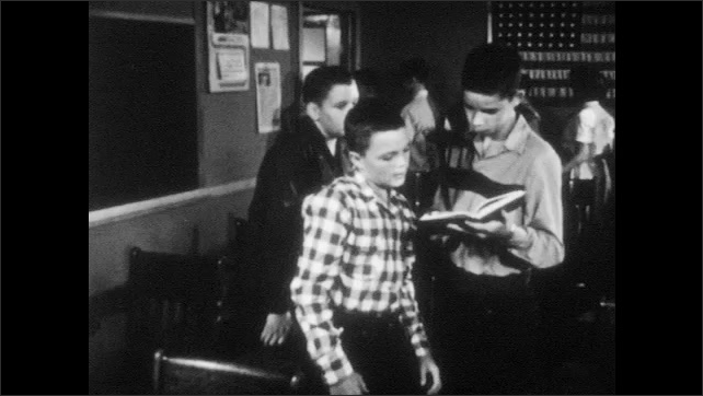 1950s: High school students sit in classroom. Teacher talks, students stand up and leave classroom. Boy shows book to friend. Boy puts hands into trash can, smoke comes out. Three boys start to cough.