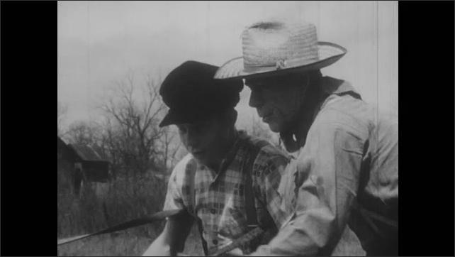1950s: Man fastens strap around boy, talks to boy. Boy holds plow, man walks alongside boy.